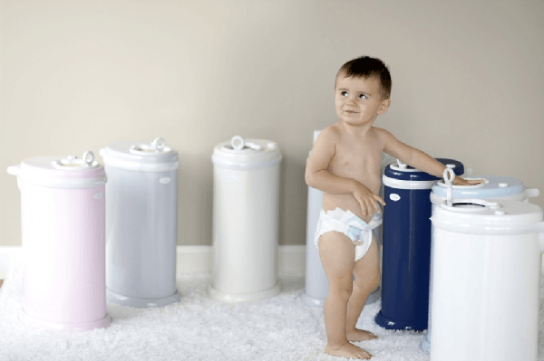Baby among variously colored diaper pails