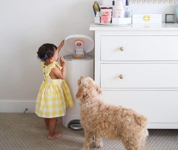 Baby with a diaper pail in the nursery with dog watching