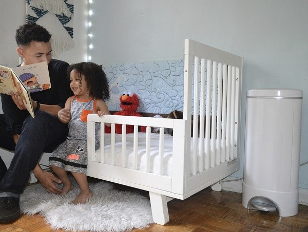 Brother reading a book to baby sister in the nursery